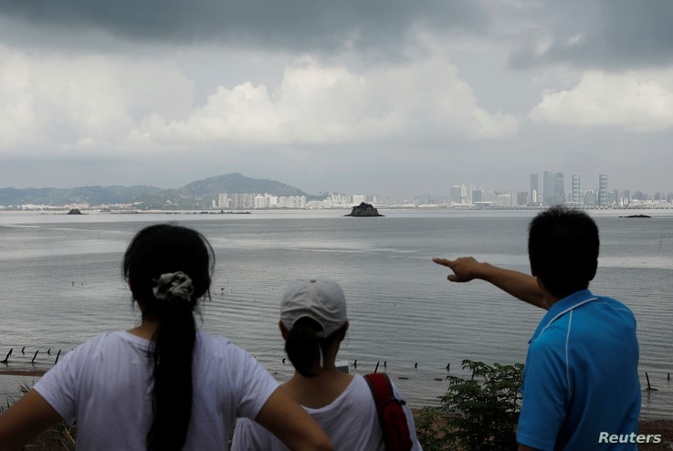 FILE - A tourist points China's Xiamen from a former military fort, ahead of the 60th anniversary of Second Taiwan Straits Crisis against China, on Lieyu island, Kinmen county, Taiwan, Aug. 20, 2018.