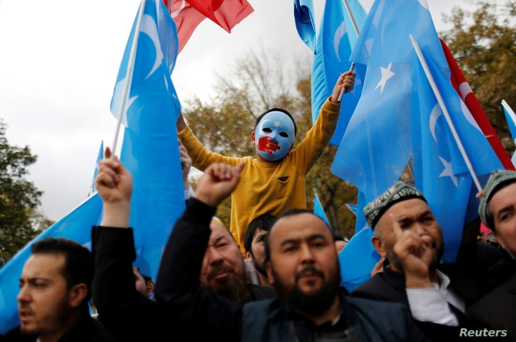 A masked Uighur boy takes part in a protest against China, at the courtyard of Fatih Mosque, a common meeting place for pro…
