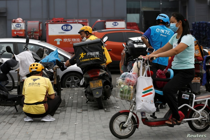 A woman wearing a face mask rides an electric bicycle with her groceries past delivery workers of Meituan and Ele.me, following…