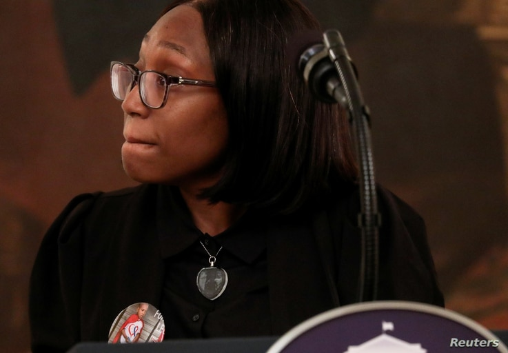 Charron Powell, whose son LeGend Taliferro was shot and killed in Kansas City in June, wears a button honoring her late four…