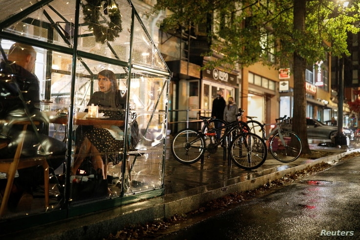 Restaurant patrons sit inside plastic tents while being served outside of the Lupo Verde restaurant along the 14th Street…