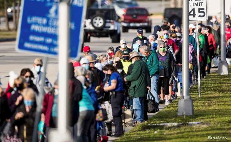 Hundreds wait in line at Lakes Park Regional Library to recieve the COVID-19 vaccine in Fort Myers, Florida, U.S. December 30,…