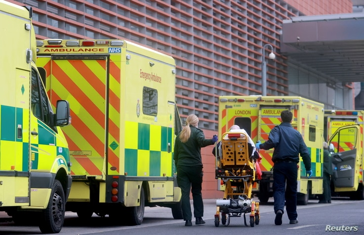 Medics transport a patient from an ambulance to the Royal London Hospital as the spread of the coronavirus disease (COVID-19)…