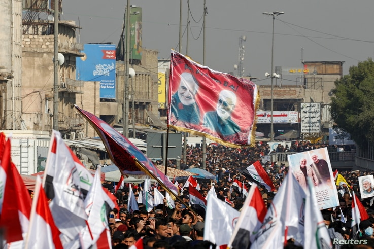 Iraqis, including supporters of Hashid Shaabi (Popular Mobilization Forces), hold flags and placards depicting senior Iranian…