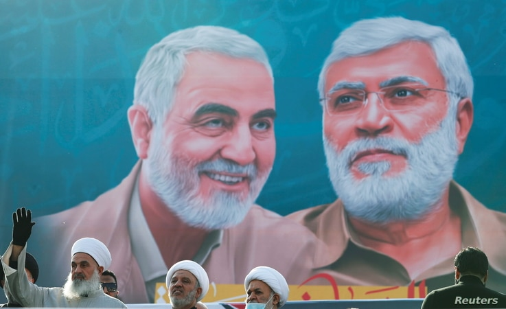 Iraqi clerics look on as they stand near a banner depicting senior Iranian military commander General Qassem Soleimani and…