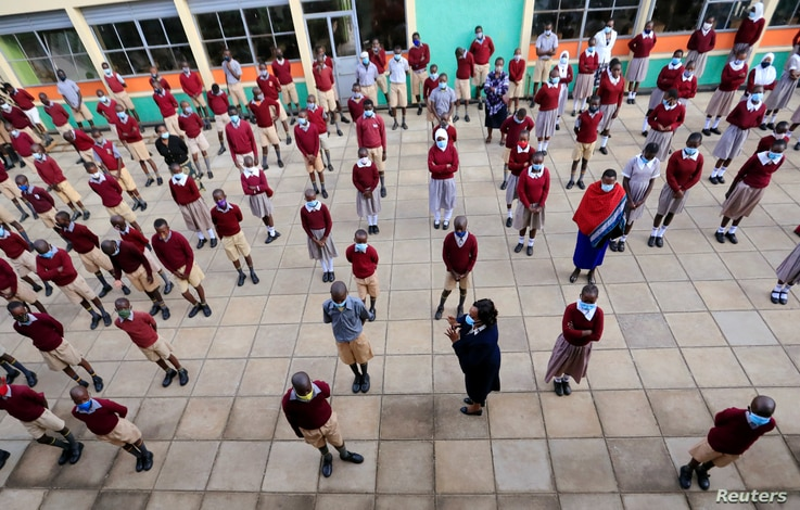 A teacher talks to schoolchildren at the morning parade at the Toi Primary School during the reopening of schools, after the…