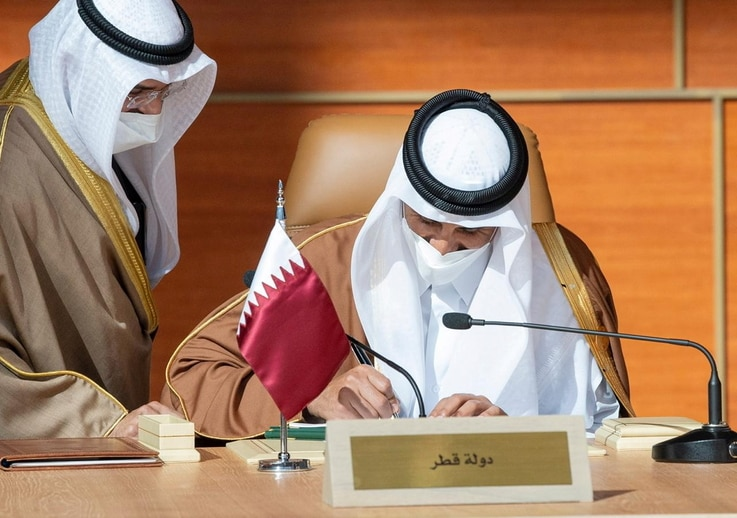 Qatar's Emir Sheikh Tamim bin Hamad al-Thani signs a document during the Gulf Cooperation Council's (GCC) 41st Summit in Al-Ula…
