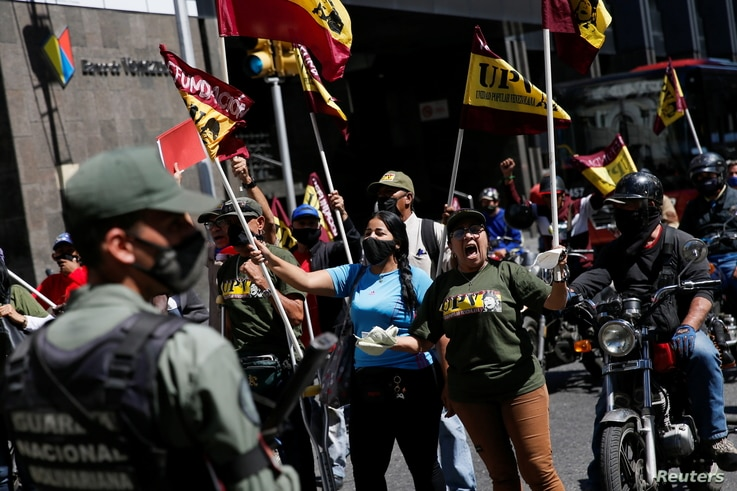 Members of Venezuelan People's Union (UPV) protest outside Venezuela's National Assembly building during the swear-in ceremony…