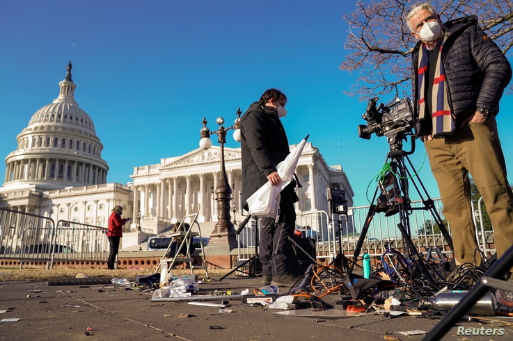 Members of the news media survey damaged equipment outside the U.S. Capitol a day after supporters of U.S. President…