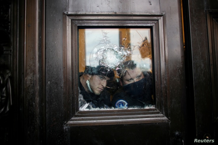 Members of the Capitol police look through a smashed window as pro-Trump protesters rally to contest the certification of the…