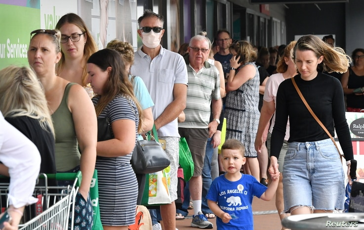People line up to enter a grocery store before an impending lockdown due to an outbreak of the coronavirus disease (COVID-19)...