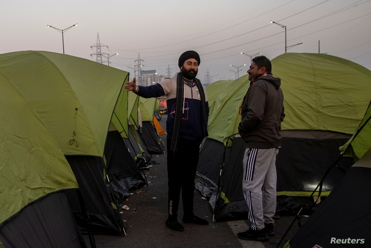 Farmers stand outside their tents at the site of a protest against new farm laws, at the Delhi-Uttar Pradesh border in Ghaziabad, India, Jan. 11, 2021.