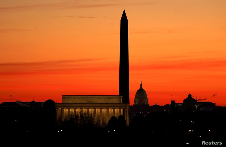 FILE PHOTO: The sky turns shades of red as the sun rises behind the U.S. Capitol, the Washington Monument and the Lincoln…