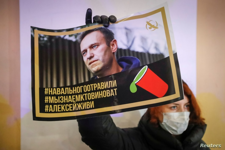 FILE - An activist holds a portrait of opposition politician Alexei Navalny during a picket in his support in St Petersburg, Russia, Dec. 22, 2020.