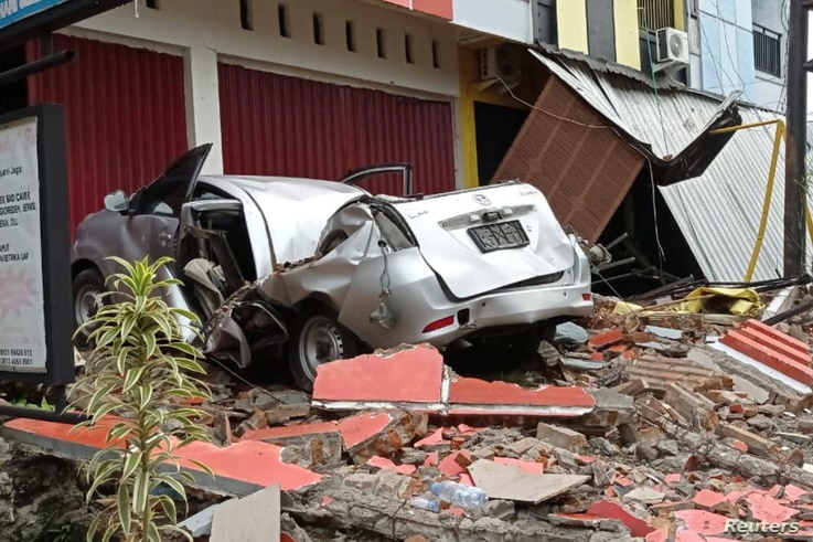 A damaged car and buildings are seen following an earthquake in Mamuju, West Sulawesi province, Indonesia, January 15, 2021 in…
