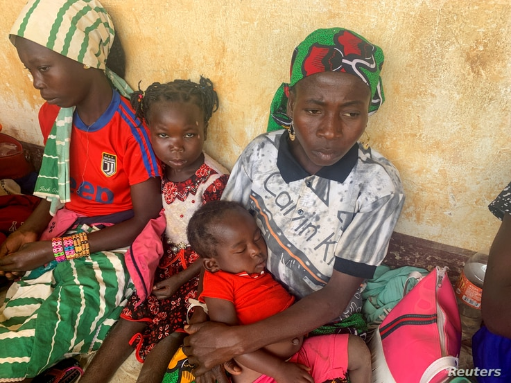 FILE PHOTO: A woman who fled the violent rebellion in Central African Republic (CAR) sits with her family as they wait for…