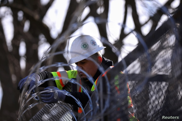 A worker installs razor wire on fencing in front of the U.S. Capitol as an extra security measure in Washington, U.S., January...