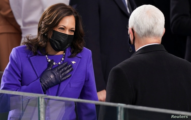 Vice President-elect Kamala Harris gestures towards U.S. Vice President Mike Pence ahead of the inauguration of Joe Biden.