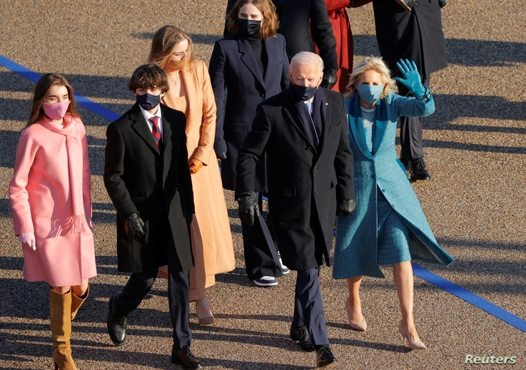 U.S. President Joe Biden, his wife Jill and members of their family walk to the White House during the Inauguration Day parade,…
