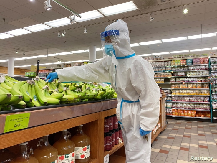 A shopper wearing a personal protective suit, mask and face shield shops for bananas at a Whole Foods Market during the…