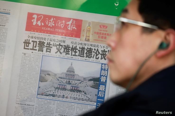 A man stands in front of a copy of the Global Times newspaper featuring an image of the U.S. Capitol during preparation for the inauguration of Joe Biden as the U.S. president, which is placed on a public display window in Beijing, China, Jan. 21, 2021.