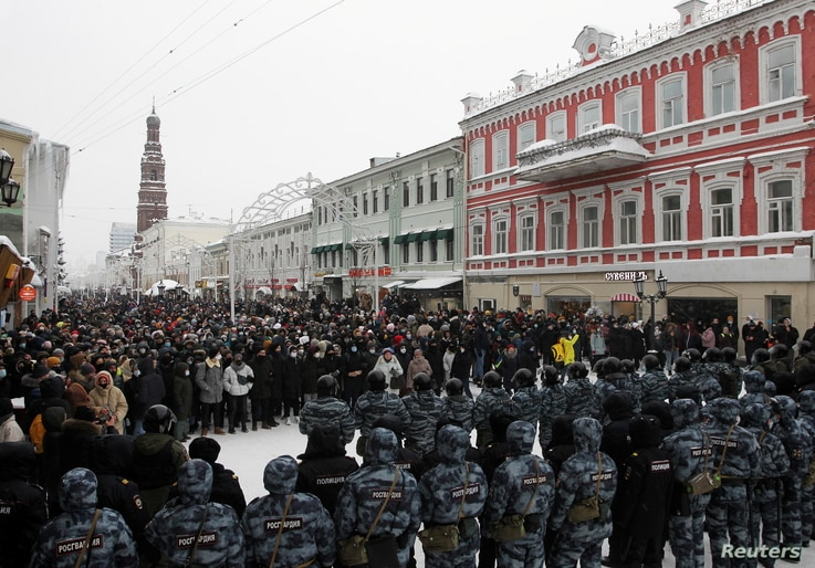 Law enforcement officers stand in front of participants during a rally in support of jailed Russian opposition leader Alexei Navalny in Kazan, Russia, Jan. 23, 2021.