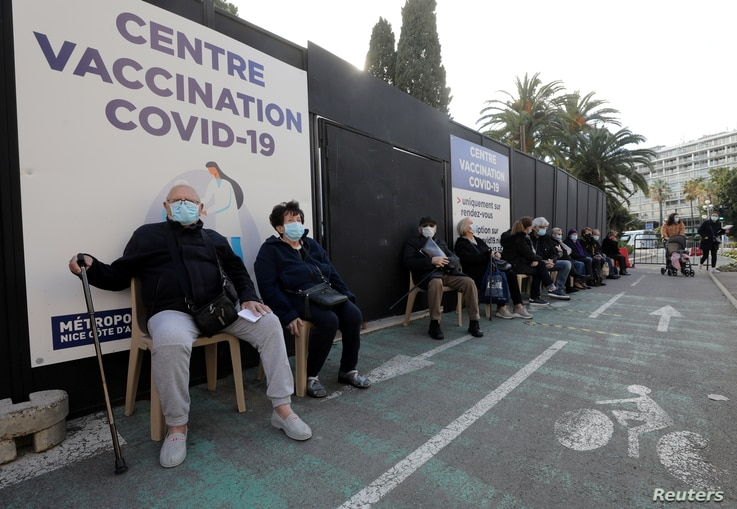 Senior citizens, wearing protective face masks, wait at a coronavirus disease (COVID-19) vaccination center in Nice, France,…
