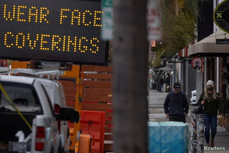 People walk past a sign warning to wear masks after California lifted its regional stay-at-home orders during the outbreak of…