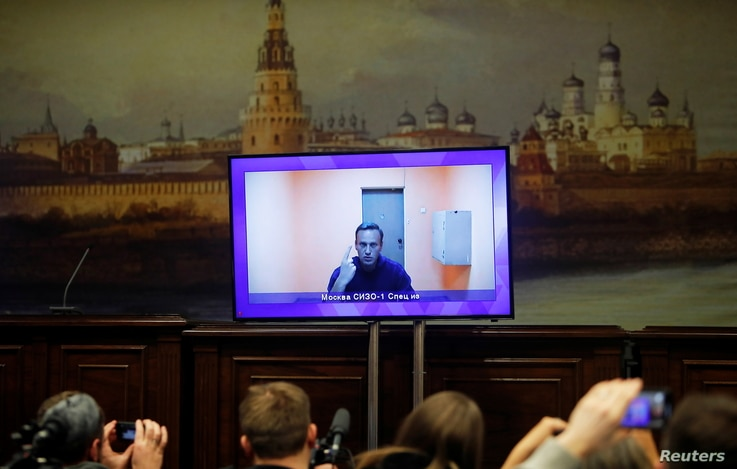 Russian opposition leader Alexei Navalny is seen on a screen via a video link during a court hearing to consider an appeal on…