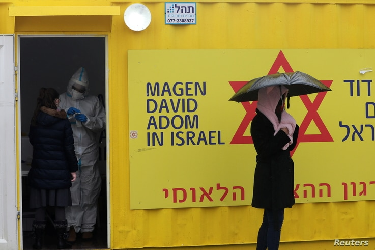 A woman waits outside a container at a coronavirus testing center while Israel is under a lock down as part of the coronavirus…
