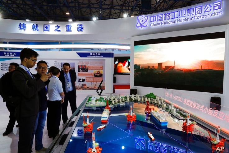Staff members from the China National Nuclear Corporation attend foreign visitors as they look at the models of oil tanker...