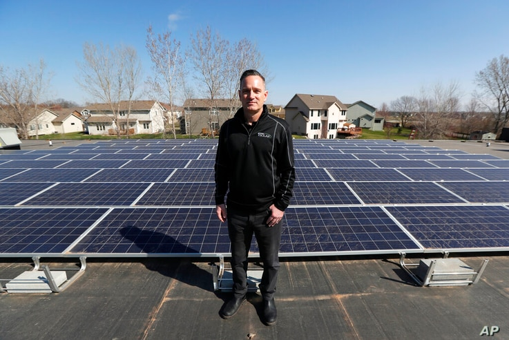 In this April 15, 2019, photo, Todd Miller stands next to solar panels on the roof of his solar installation business in Ankeny…