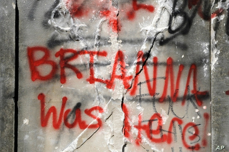 Graffiti is show on the damaged base of a Confederate memorial that was removed overnight in Birmingham, Ala., on Tuesday, June…