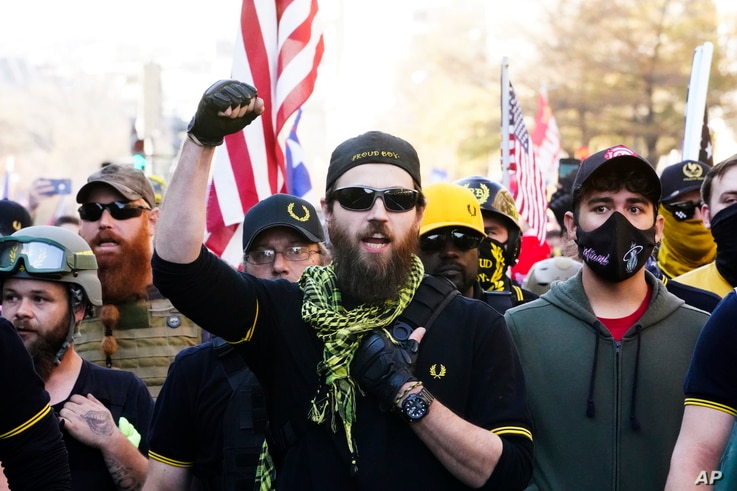 People identifying themselves as members of the Proud Boys join supporters of President Donald Trump as they march Saturday Nov…