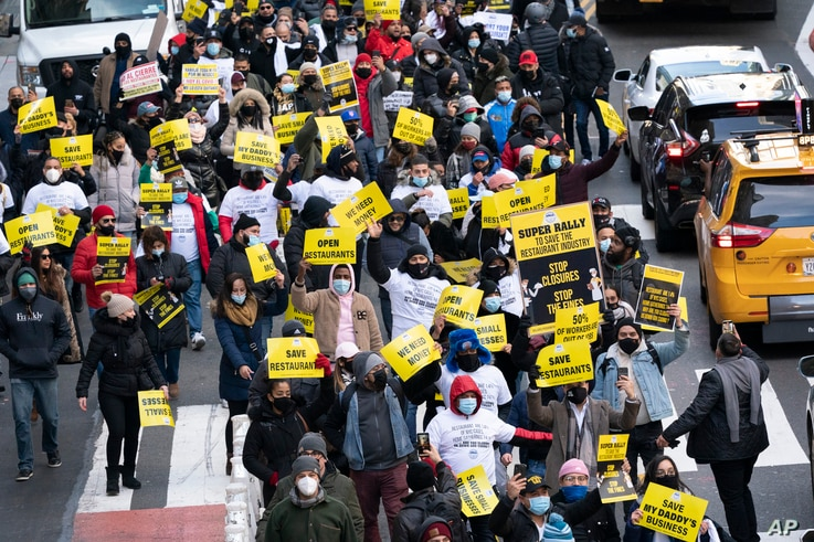Restaurant and bar owners, employees and union workers march on 42nd Street in support of the restaurant industry, Tuesday, Dec…
