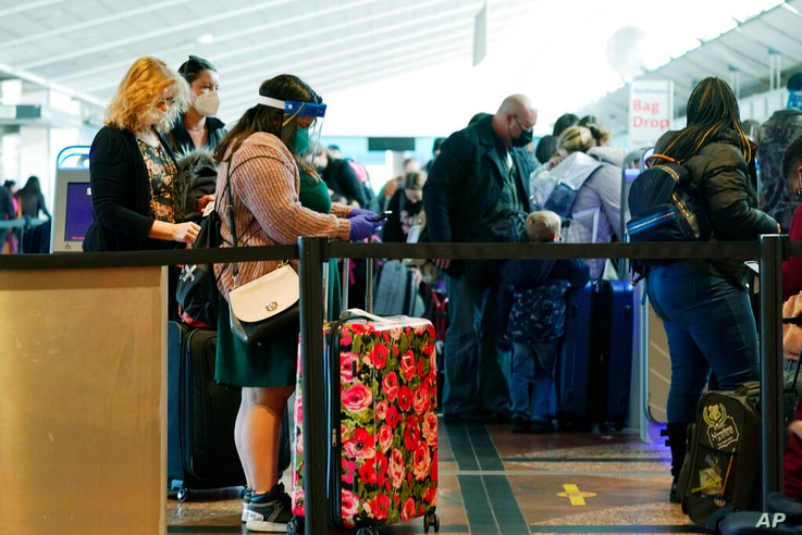 Travellers wear face masks while waiting at to check in at the Southwest Airlines counter in Denver International Airport…
