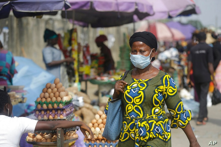 A woman wearing a face mask to protect against coronavirus, walks on a street, in Lagos, Nigeria , Thursday, Dec. 31, 2020. A...