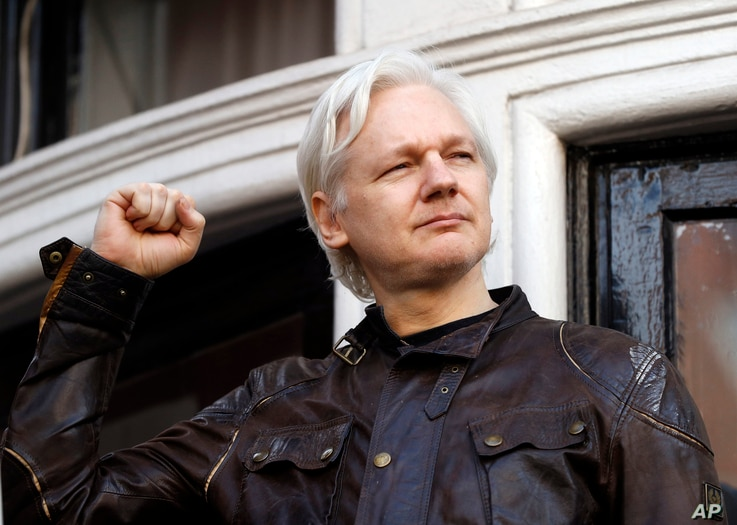 FILE - In this May 19, 2017 photo, WikiLeaks founder Julian Assange greets supporters outside the Ecuadorian embassy in London.