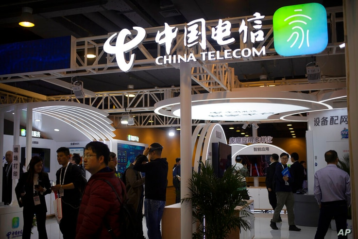 Visitors look at a display from Chinese telecommunications firm China Telecom at the PT Expo in Beijing, Thursday, Oct. 31,…