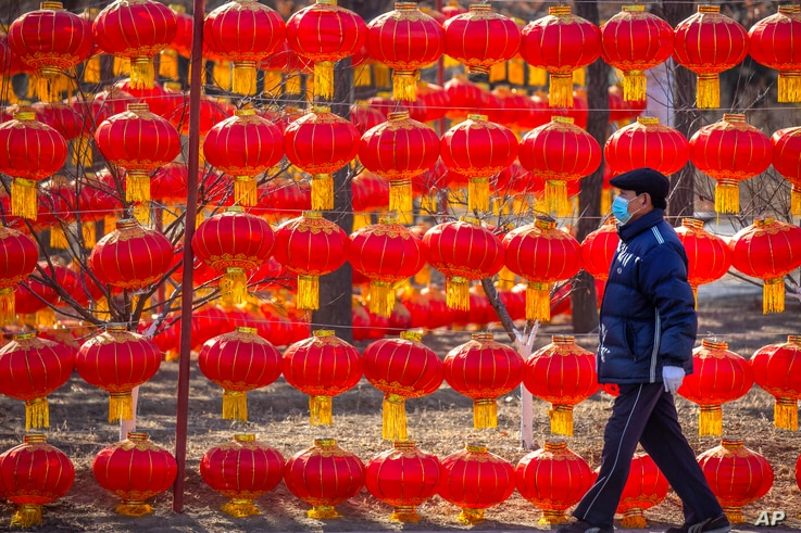 A man wearing a face mask to protect against the spread of the coronavirus walks past a display of lanterns at a public park in Beijing, Jan. 5, 2021.