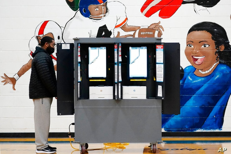 A person casts their vote during Georgia's Senate runoff elections on Tuesday, Jan. 5, 2021, in Atlanta. (AP Photo/Brynn…
