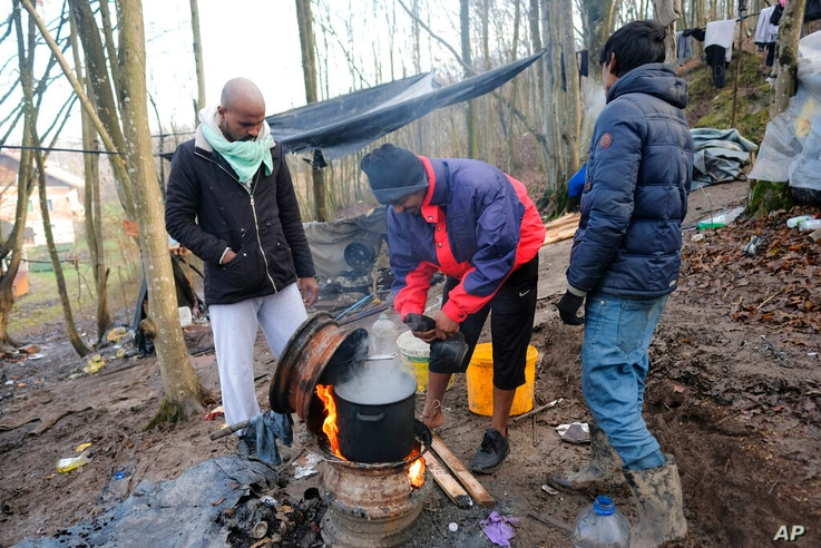 Migrants cook on a stove improvised from wheel rims at a makeshift camp in a forest outside Velika Kladusa, Bosnia, Tuesday,…