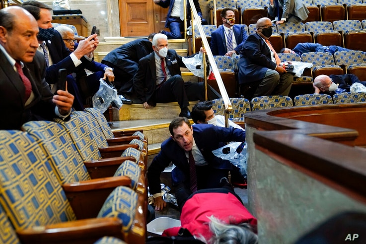 People shelter in the House gallery as protesters try to break into the House Chamber at the U.S. Capitol on Wednesday, Jan. 6,...