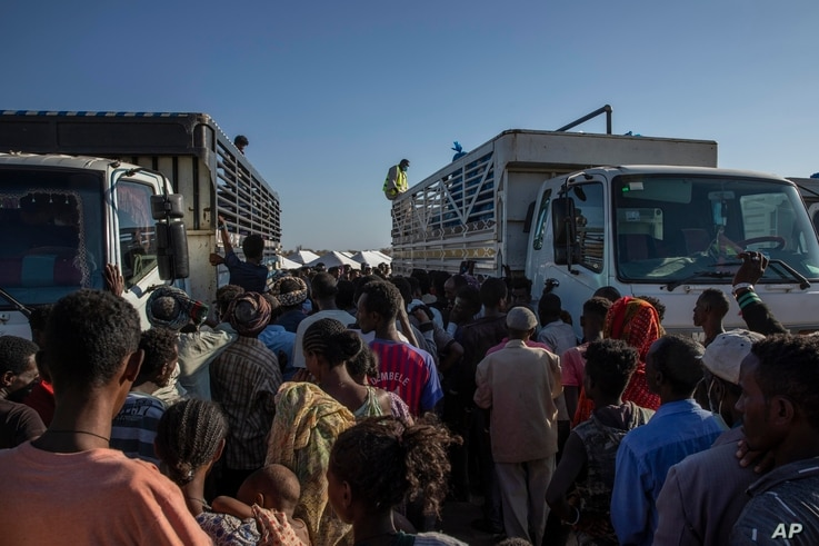 FILE - Tigray refugees who fled the conflict in Ethiopia's Tigray region, wait to receive aid at Umm Rakouba refugee camp in Qadarif, eastern Sudan, Nov. 24, 2020.