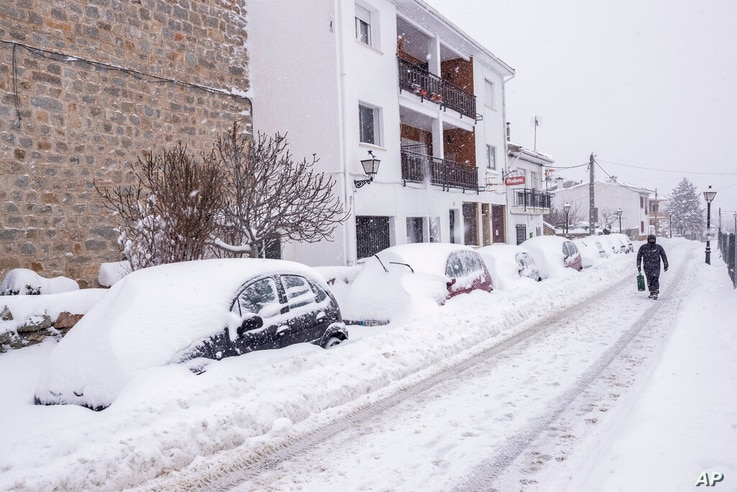 A man walks under a heavy snowfall in Bustarviejo, outskirts of Madrid, Spain, Saturday, Jan. 9, 2021. A persistent blizzard…