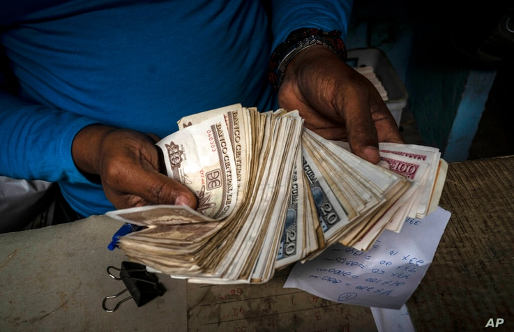 FILE - In this Dec. 11, 2020 file photo, a worker shows a wad of Cuban pesos in Havana, Cuba, Friday, Dec. 11, 2020. In 2021,...