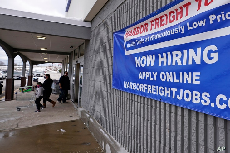 """FILE - In this Dec. 10, 2020, file photo, a """"Now Hiring"""" sign hangs on the front wall of a Harbor Freight Tools store in…"""
