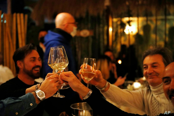 Customers toast as they dine in a restaurant in Milan, Italy, Friday, Jan. 15, 2021. The restaurant is one of various that…