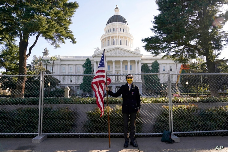 Christian Alvarado holds an American flag in front of a temporary six-foot high chain link fence surrounding the...