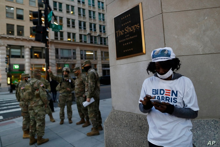 A Biden-Harris supporter stands at a corner as National Guards deploy around the city ahead of President-elect Joe Biden's...